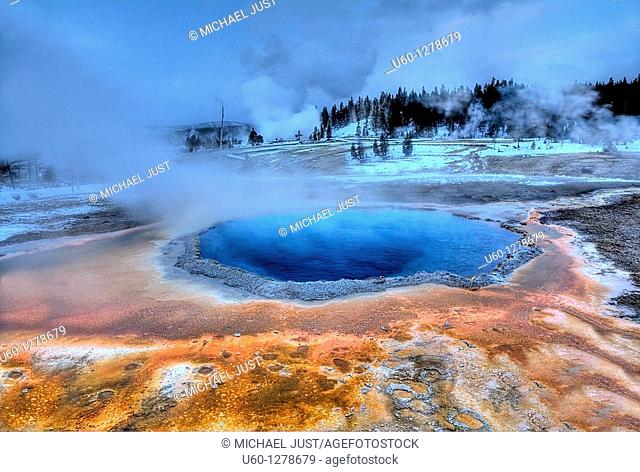 Crested Pool's colors shine during the winter at Yellowstone National Park as Grand Geyser erupts in the background