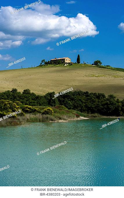Typical green Tuscan landscape in Val d'Orcia, farm on hill, lake and blue cloudy sky, La Foce, Tuscany, Italy