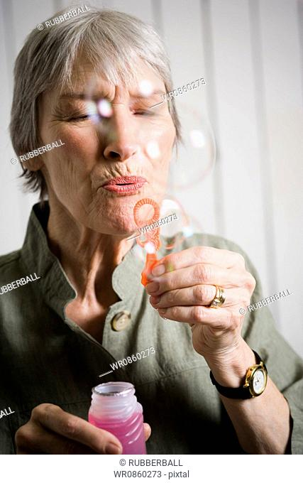 Portrait of an elderly woman blowing bubbles with a bubble wand