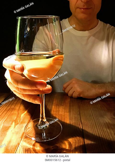 Man drinking a glass of white wine