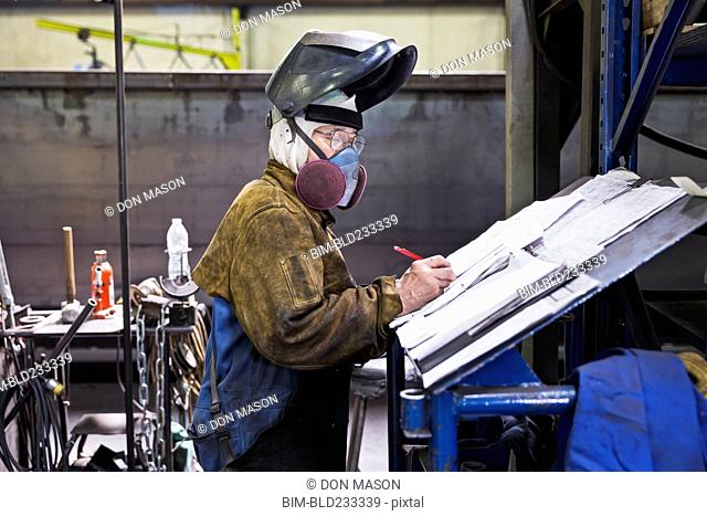 Asian worker wearing mask writing on paperwork in factory