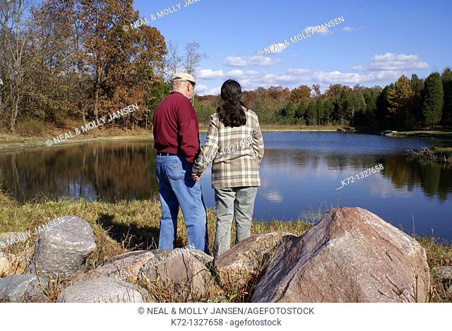 Senior couple holding hands looking at lake