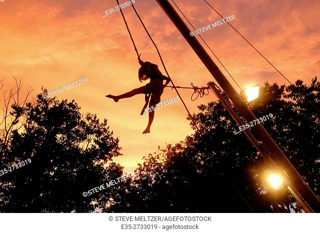 A young girl on rope swing at sunset