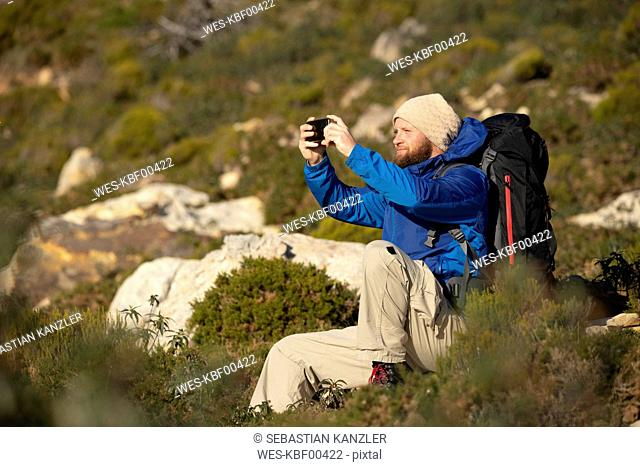 Spain, Andalusia, Tarifa, man on a hiking trip sitting down taking a selfie