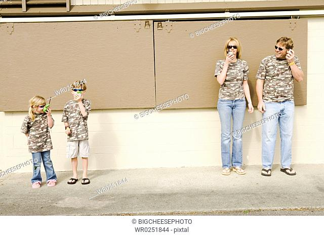 Family in camouflage playing with radios