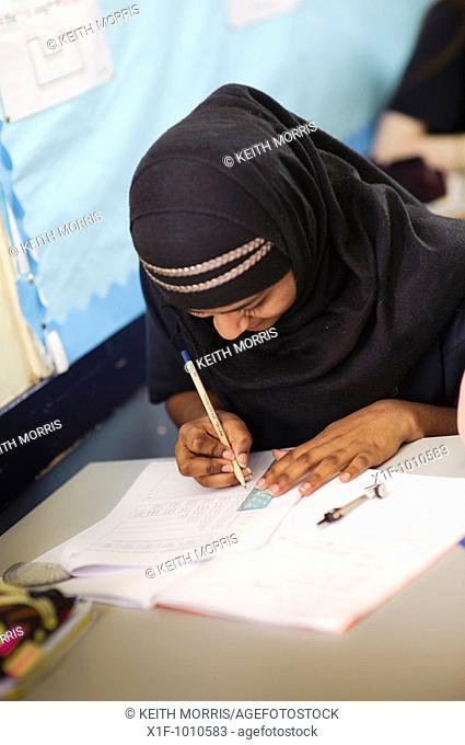 Teenage muslim girl in mathematics class, secondary school, Wales UK