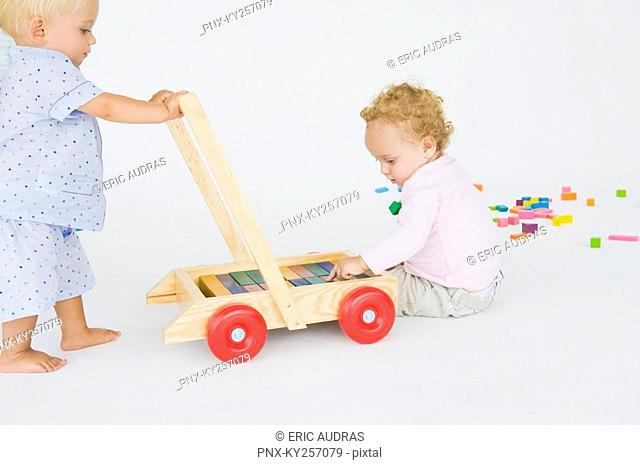 Two baby boys playing with a push cart