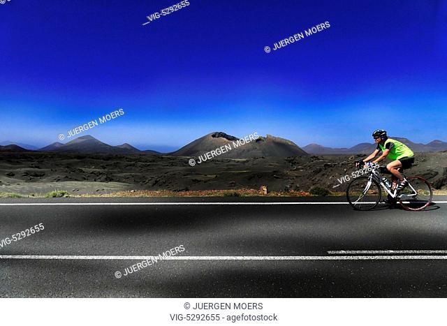 25.02.2015, Spain, ESP, Canary Islands, Lanzarote, Yellow dressed young woman moves on bike through the fire mountains in the Parque Nacional de Timanfaya