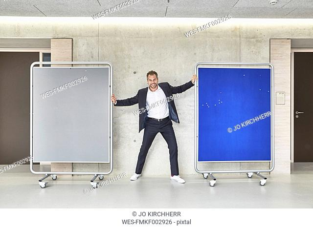Smiling businesssman standing between two movable boards