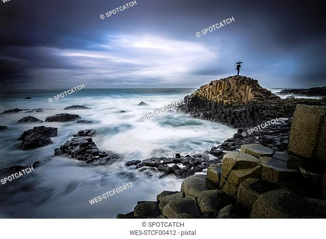United Kingdom, Northern Ireland, person on rock at Giant's Causeway