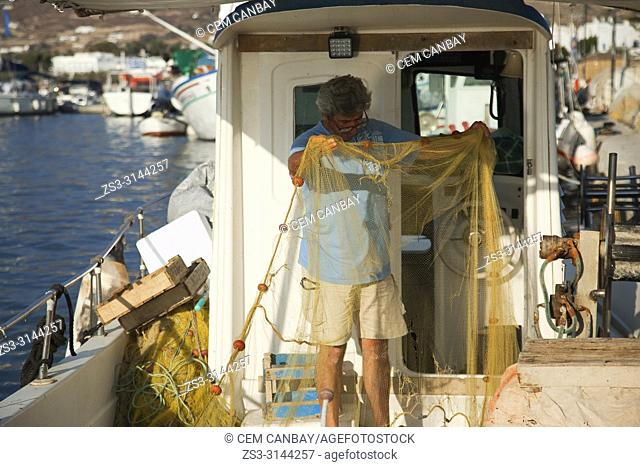 Fisherman mending nets in his traditional fishing boat at the harbour of the Naoussa village, Paros Island, Cyclades Islands, Greek Islands, Greece, Europe