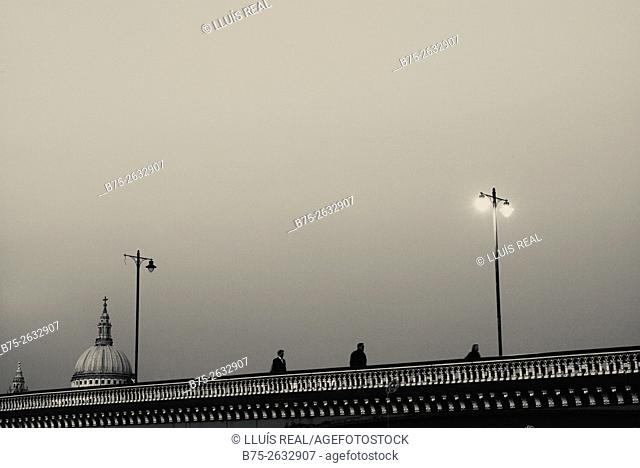 Unrecognizable people walking trough the Blackfriars Bridge with two lighted lamp post and the Saint Pauls Dome in the background