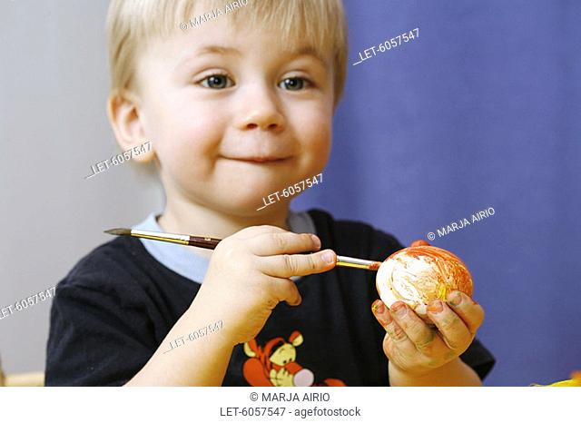 Boy painting Easter eggs