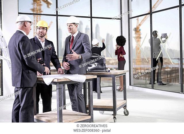 Businessmen talking in office under construction
