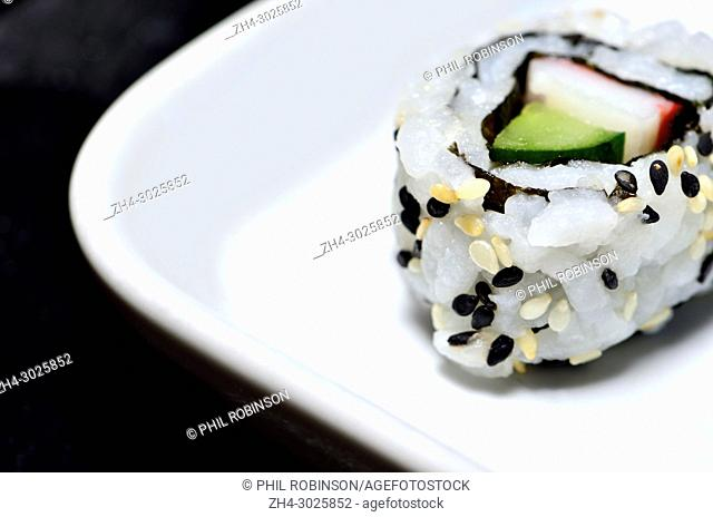 Sushi on a white plate: uramaki (roll with rice on the outside)
