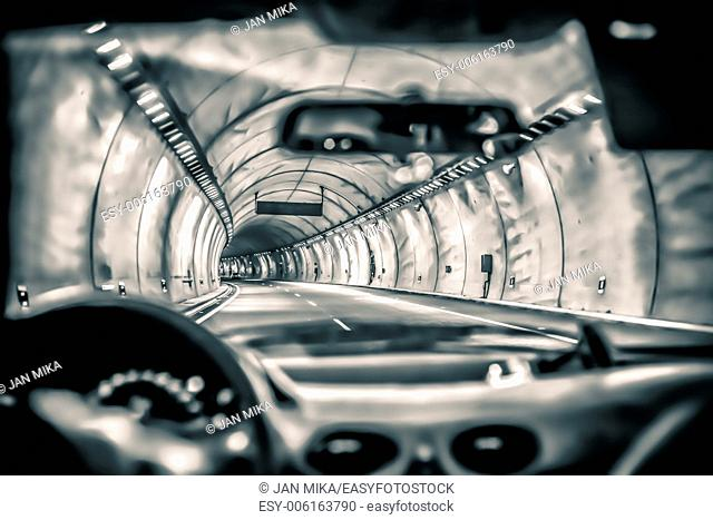 Abstract toned photo of a car driving through highway tunnel