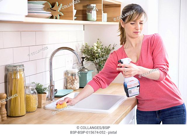 Woman using a conventional cleaning product