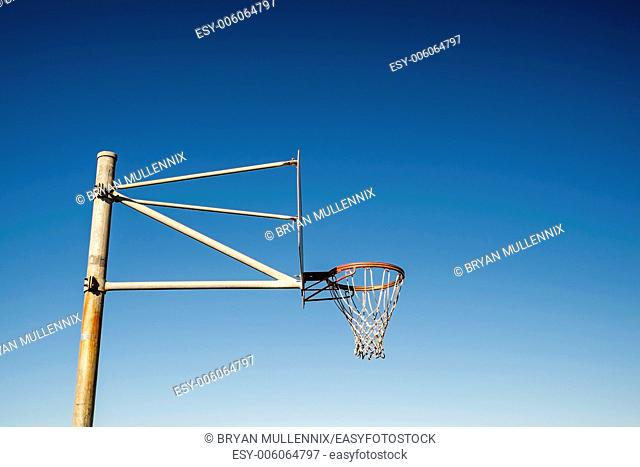 Side view of a basketball hoop against blue sky