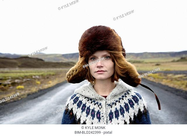 Caucasian woman wearing sweater and fur hat in middle of road