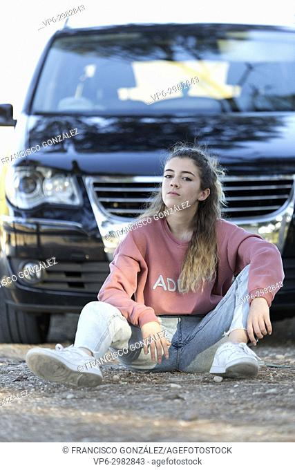 Teenager sitting on the floor in front of a car. Vertical shot with natural light