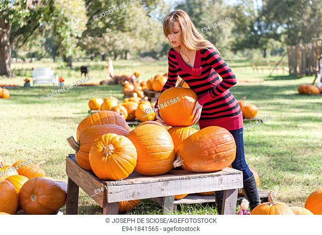 30 Year old redheaded woman with pumpkins in autumn