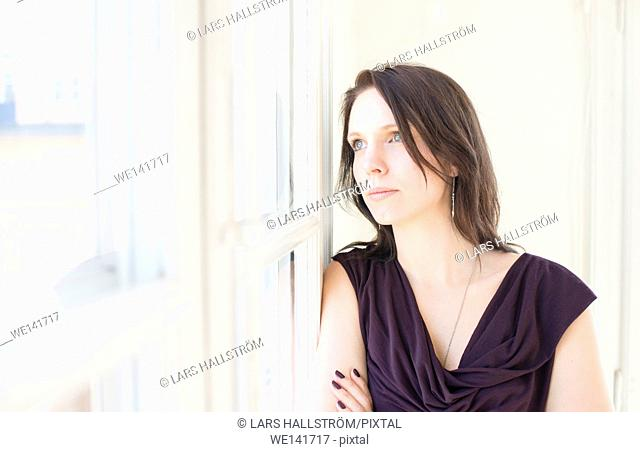 Woman in black dress standing by a window, looking away. Concept of loneliness, serious thinking and sadness