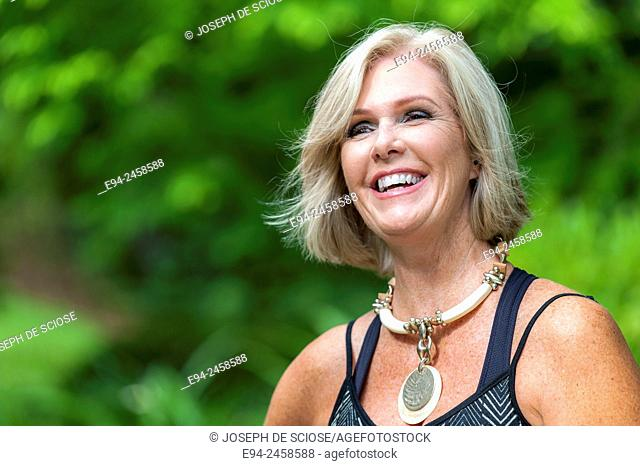 A portrait of a smiling 56 year old blond woman looking away from the camera, outdoors