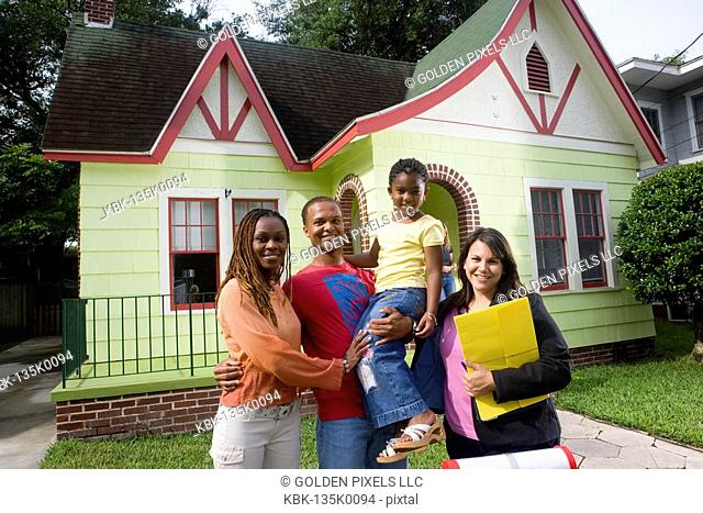 Portrait of family standing outside house with real estate broker