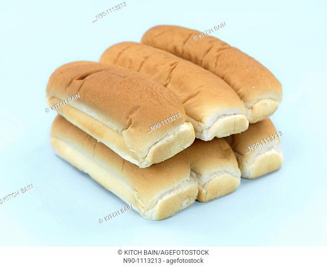 Plain hotdog buns isolated against a blue background