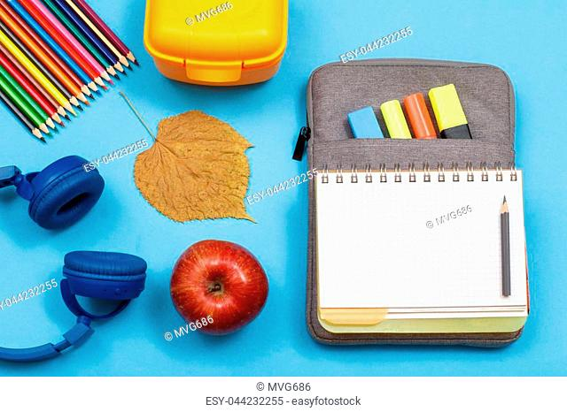 Headphones, color pencils, apple, dry leaf, lunch box, open exercise book on bag-pencil case with color felt pens and marker on blue background