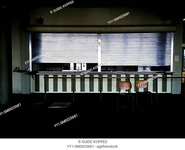 Rotterdam, Netherlands. Roller shutters and tow chairs shielding a kitchen area inside an abandoned industrial corporation's employee cantine