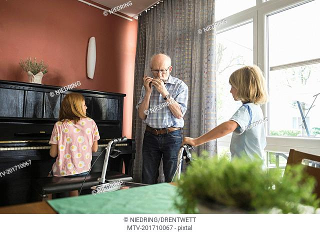 Grandfather playing musical instrument with children