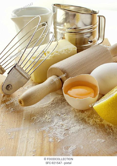 Various baking utensils, eggs, butter and lemon