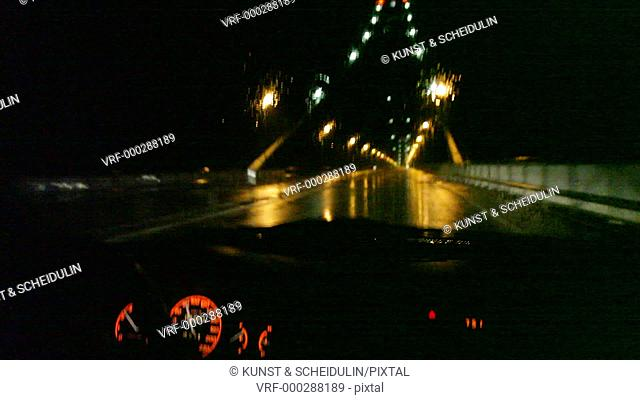 Driving through over the Höga Kusten Bro (High-Coast Bridge) suspension bridge at night in a car while heavy rain is splattering against the windshield and...