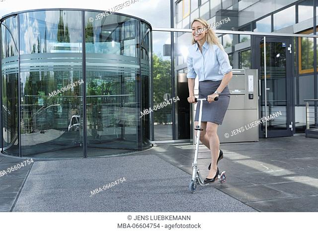 blond businesswoman with Scooter in front of entrance of an office building