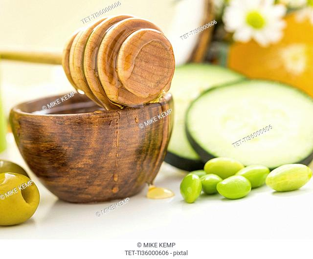 Honey dipper on bowl, olives, peas and slices of cucumber