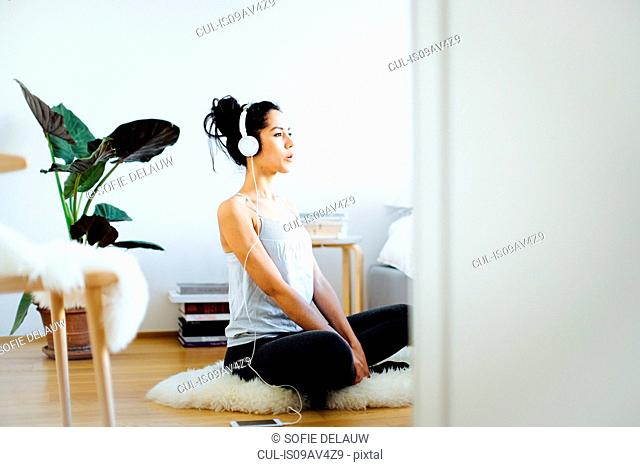 Young woman practicing yoga in living room whilst listening to headphones