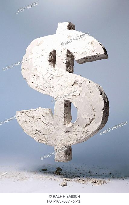 Dollar sign made of stone material levitating against gray background