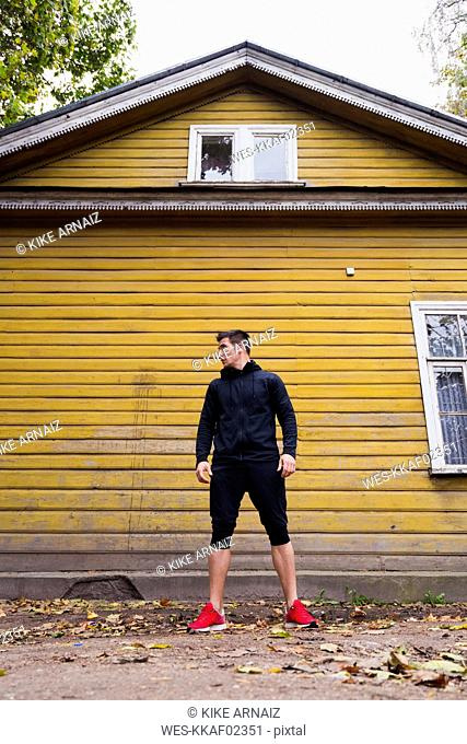 Athlete standing in front of a yellow wood house