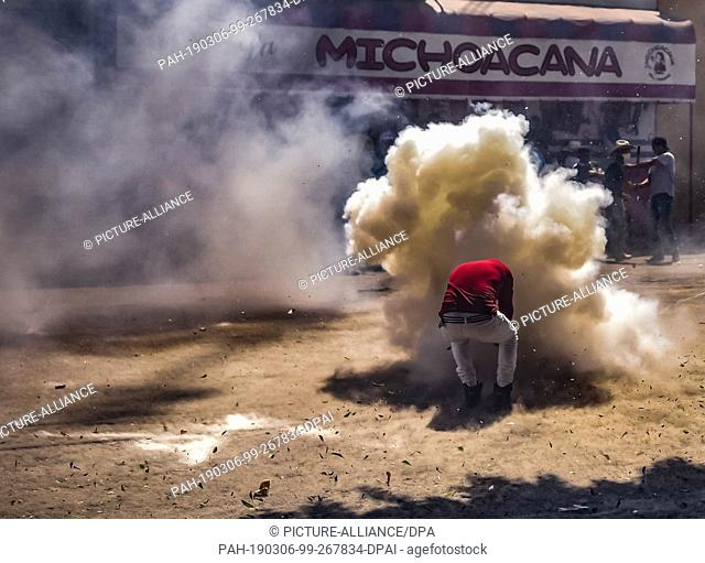"05 March 2019, Mexico, San Juan de la Vega: Smoke rises when a participant of the """"Festival of Explosive Hammers"""" hits a plate with his hammer"
