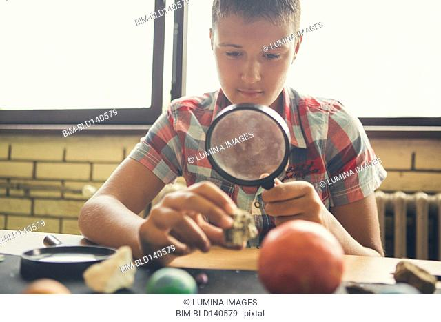 Student examining models of planets in classroom
