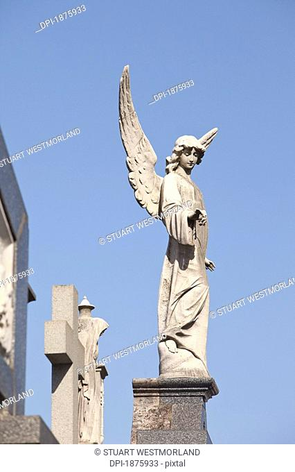 Buenos Aires, Argentina, Angel Statues And A Cross Made Of Stone On Top Of Tombs In The Recoleta Cemetery