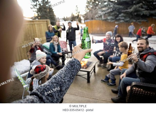 Woman with beer bottle toasting family and neighbors at fire pit in snowy driveway