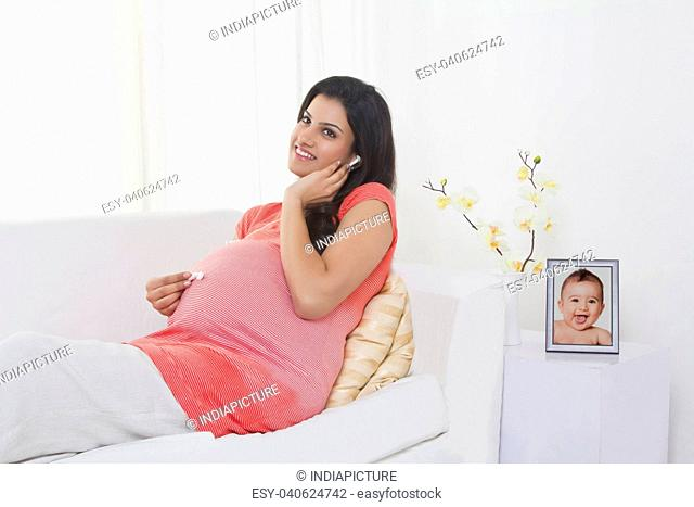 Pregnant woman putting earphones on stomach
