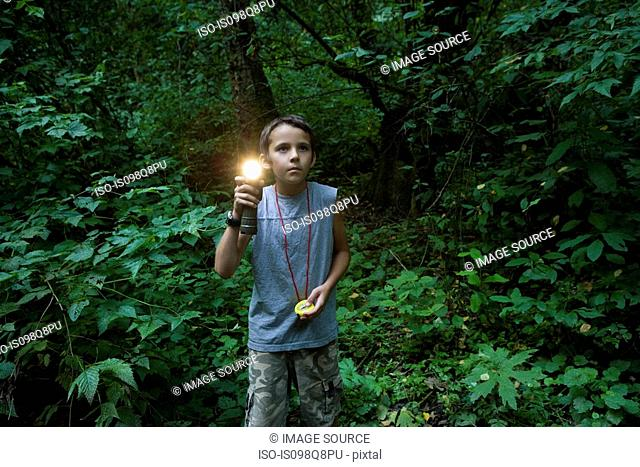 Boy with torch in forest