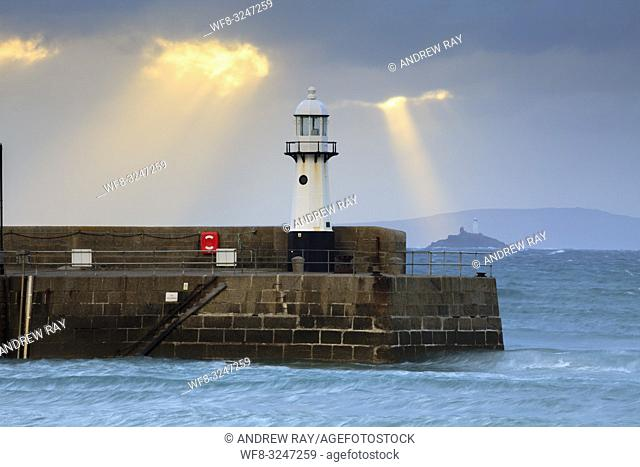 Shafts of light behind the lighthouse on Smeaton's Pier at St Ives in Cornwall, with Godrevy Island and lighthouse in the distance