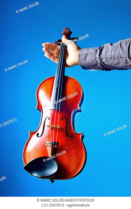 Violin held by a hand of a musician. Music, musical instrument