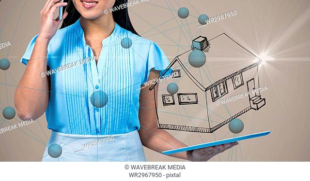 Midsection of woman talking on mobile phone while holding digital tablet with house symbol and conne