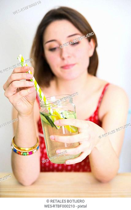 Woman holding glass of detox water infused with lemon and cucumber