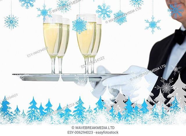 Waiter carrying tray full glasses of champagne against snowflakes and fir trees